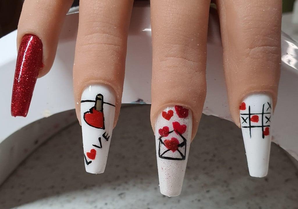 Nail-Art handgemalt mit verschiedenen Valentinstags-Muster auf Gelnägel